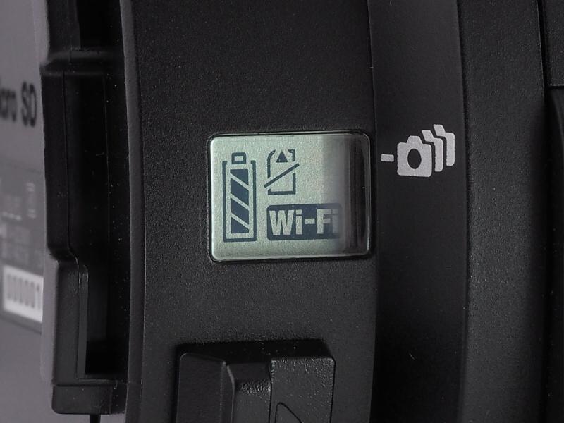 本体側面の液晶には、Wi-Fi接続や電池残量、記録カード用警告などが表示される。下のレバーはアタッチメント解除用