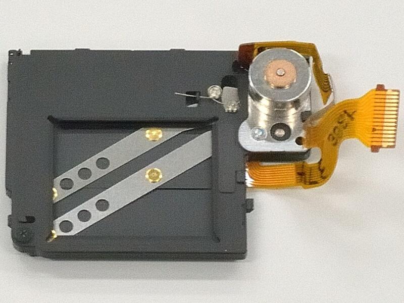 """<strong class="""""""">後幕をモーターで動かすシャッター機構</strong><br class="""""""">先幕の電子化と、後幕もモーターで動かす簡易型にしてシャッターユニットを大幅に小型化。1/500秒を超える高速側は電子シャッターで露光制御する"""