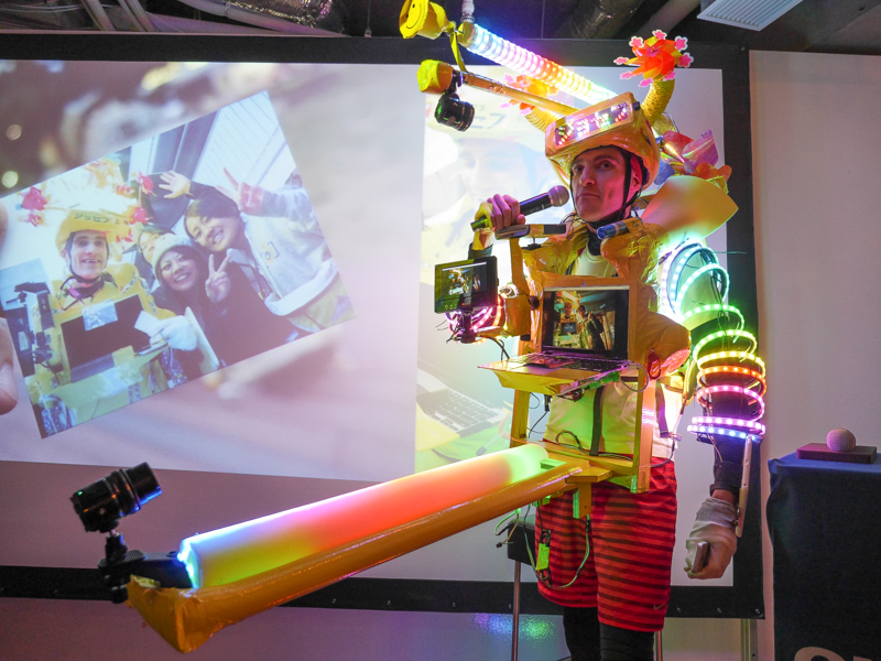 """人物に装着してセルフ撮影する""""ウェアラブルシステム""""の例。写真のジョセフ氏はこのシステムで東京マラソンに参加し、走りながら中継するという"""