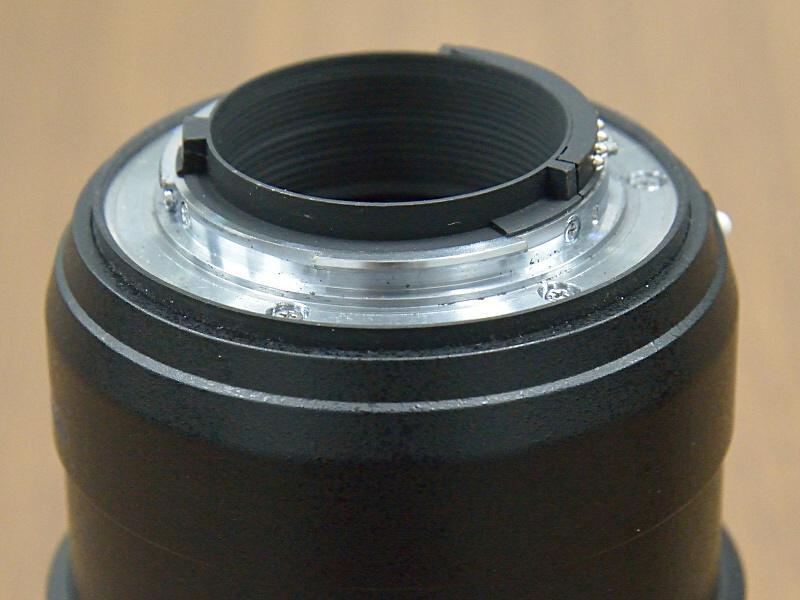 """<strong class="""""""">電磁絞りとメカ連動方式の絞りの違い</strong><br class="""""""">従来のニッコールレンズ(上)はマウント部に絞りレバーがあり、このレバーをカメラボディ側から動かして絞りを開閉させている。一方、電磁絞り(下)は電気接点を使って電気的に絞りを動作させる"""