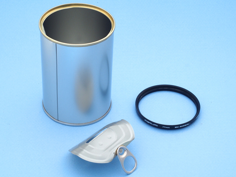 貯金缶は普通の缶詰と同じく、プルタブを引くとフタをパッカンと外すことができる。この開いた缶の口に、77mm径のフィルター枠(ジャンク品のガラスを外したもの)がすっぽりはまるのがミソである