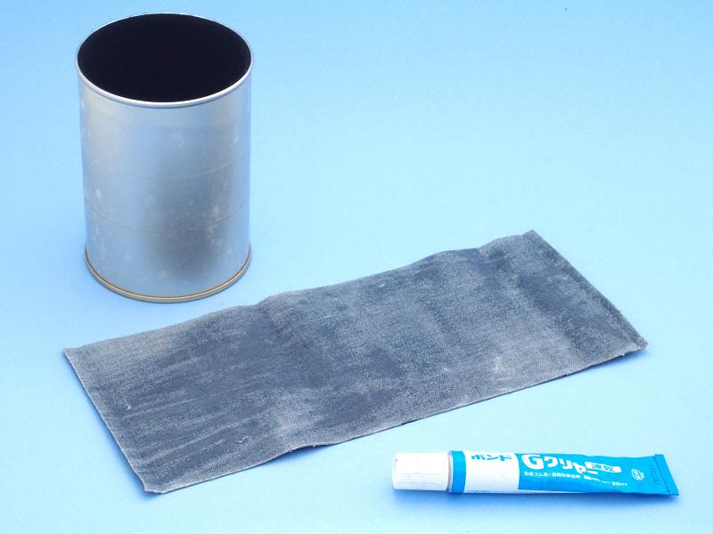 ポーチをばらして革だけにして、測ったサイズにカットする。しかし、この合成皮革は裏面が布地になっていて、両面テープで接着してもすぐ剥がれてしまう。そこでちょっと思案して、缶の表面に両面テープを貼り、布地にボンド「Gクリヤー」を塗布することにした。Gクリヤーを布地に薄く塗って乾かすと、両面テープへの食いつきが良くなると睨んだのである