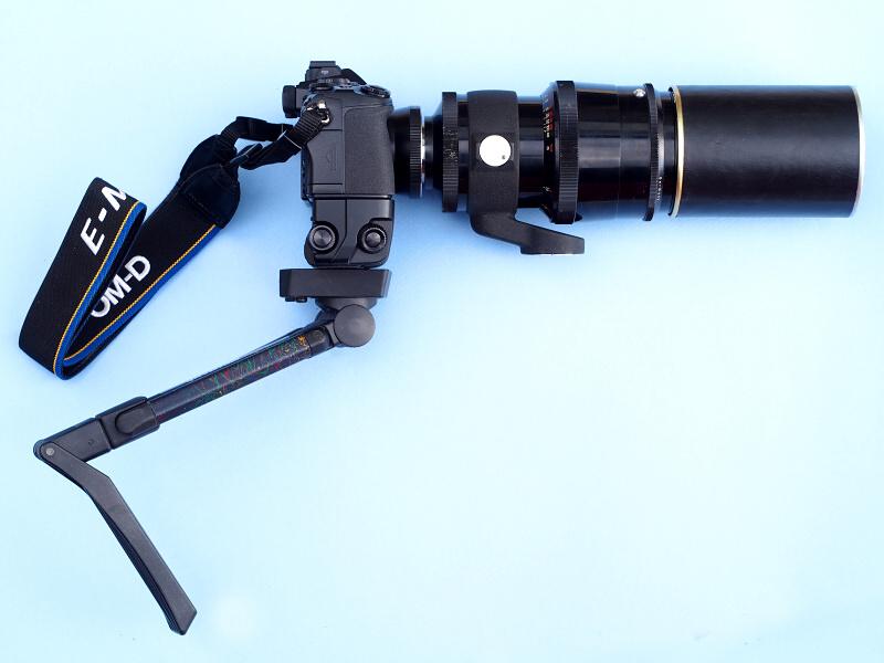 """ガンストックを装着すると、まさに""""銃器""""といった感じのスタイルになった。ちょっと人目を憚られる外見だが、グリップを胸に当ててカメラを構えると、安定性は確実に増す。実は、1936年発売のオリジナルタイプCarl Zeiss Jena 180mm f2.8にはCONTAX IIに装着するライフル銃そっくりの撮影システムがあって、それにあやかってみたのだった"""