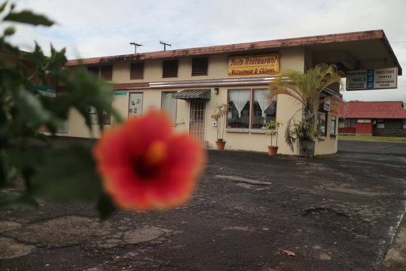 ピントを古いレストランに合わせる。手前にぼけたハイビスカスがあることで、この場所が南国であることが分かる。赤い色が差し色となった