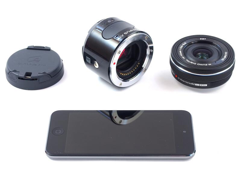 OLYMPUS AIR A01のカメラ本体(後中)は操作部として電源ボタン、シャッターボタン、レンズマウントのみを備える。構図確認を含むカメラ操作はWi-Fiで接続したスマートフォンによって行い、これを本体に装着するためのアダプター(後左)も付属している。レンズはマイクロフォーサーズマウントなら何でも装着できる。なお、今回は発売直前のOLYMPUS AIR A01をお借りしたため、スマートフォンのかわりにアプリがインストールされたiPod touch を使用する
