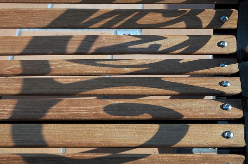 街中のベンチに手すりの影が落ちている。木目が五線譜に、影がト音記号に見えた。