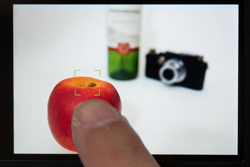 タッチAFに設定し、手前のリンゴにタッチ。背景のカメラとボトルがボケている。