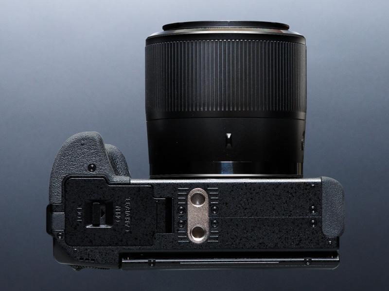三脚穴はレンズの光軸からずれている。三脚穴の手前に、ビデオカメラでおなじみのVHSピンの穴を備える点はユニークだ。動画機能重視のためだろう