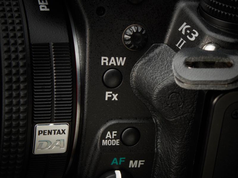 Raw/Fxボタンは、レンズを支える左手の親指を少しずらしたところにある。
