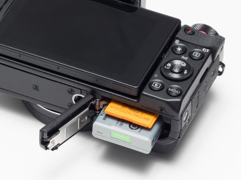 バッテリー/メモリーカード室の蓋はカメラ本体方向に沿って開くため、交換時は三脚およびネジ穴で吊り下げるタイプのストラップは必ず取り外す必要がある。バッテリーはNB-13L。対応メモリーカードはSDXC/SDHC/SDメモリーカード(UHS-I対応)