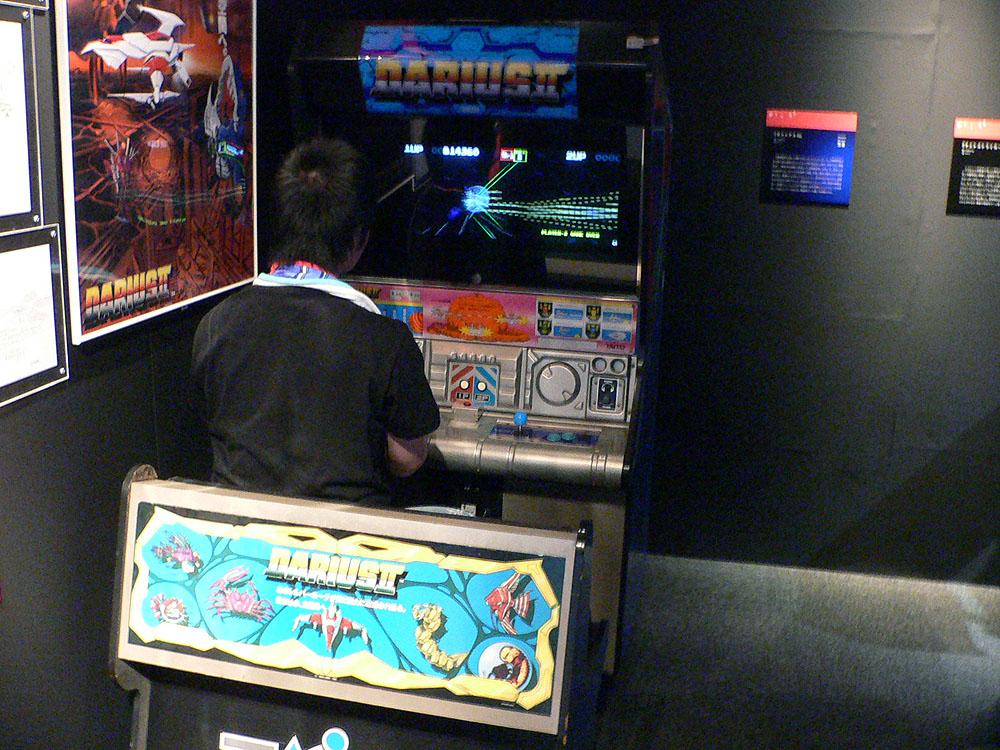タイトーの大型筐体を使用したアーケードゲーム。左が3Dシューティングの「ナイトストライカー」(1989年、タイトー)で、右は複数のモニターを横に並べて1つの大画面に見立て、ボディソニックを搭載した大型筐体を使用したシューティングゲーム、「ダライアス」の続編にあたる「ダライアスII」(1989年、タイトー)