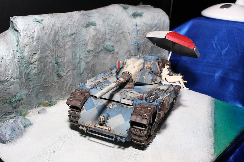 先日最新作が発売された人気シリーズの初代作品「戦場のヴァルキュリア」(2008年)より、第7小隊エーデルワイス号と水着でたたずむヒロイン、アリシアの姿を水辺のジオラマとともに制作。戦いの中の安らぎのひとときを描いている