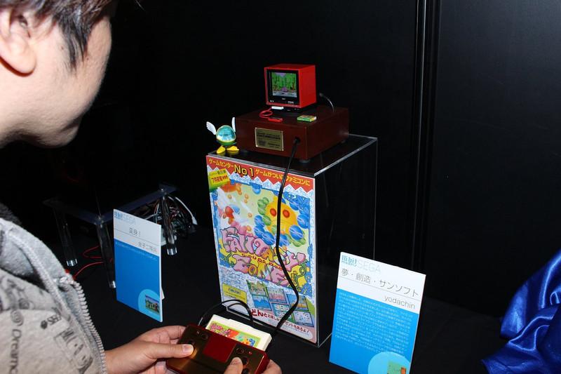 """ライバルハードで珠玉の移植度を誇ったサン電子版「ファンタジーゾーン」(1987年)のカセットを、1/6スケール「シャープ C1」とともに制作。FC互換機を組み込み、実際にゲームがプレイできる。弊誌では<a href=""""https://game.watch.impress.co.jp/docs/news/661922.html"""">タカラトミーアーツの「メガドライブメガトロン」</a>や、<a href=""""https://game.watch.impress.co.jp/docs/interview/1024248.html"""">FREEingの「namcoアーケードゲームマシンコレクション」</a>インタビューにも登場したFREEingの依田智雄氏の作品だ"""