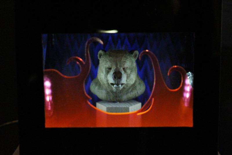 「獣王記」(1988年)のインストラクションカードが貼られた真っ黒い箱が一つ。そこから伸びたボタンを押すと、中にいる主人公がクマの獣人へと変身する。ハーフミラーとライトを使ったギミックが楽しいカラクリ箱だ