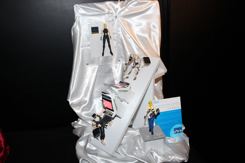 「バーチャファイター」(1993年)のアキラとサラfigmaとアストロ筐体のプラモデルを使って、制作者が作品から受けたインパクトを表現している。大伴の攻略本「バーチャファイターマニアックス」の表紙に似せたディスプレイが懐かしい