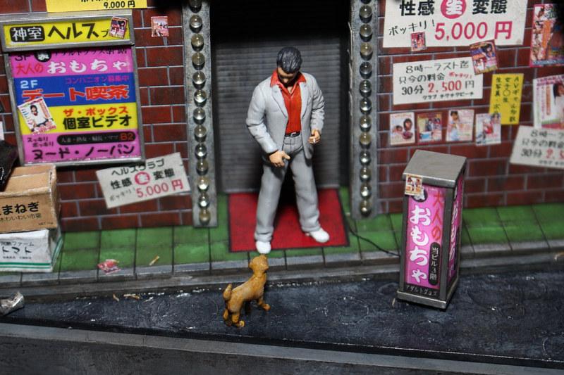「龍が如く0 誓いの場所」(2015年)の舞台となった、バブル経済に浮かれる1988年の神室町のゲームにも登場する風俗店をジオラマ化。若き日の桐生一馬が、野良犬と自分の姿を重ねている情景だ。看板やポスターの作り込みにも注目