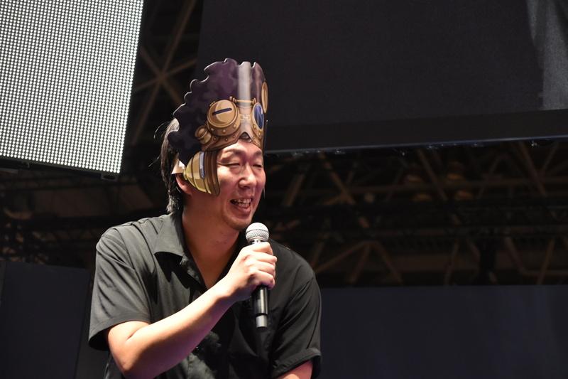 キャラクターデザインの岩元辰郎氏は、ゲームショウでもらえるメガキンのなりきりセットを身に着けての登壇
