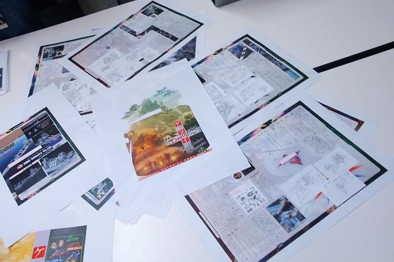 初回購入特典「OFFICIAL MATERIAL BOOK」の校正中のデザインを見つつお話を伺った。キャラクターたちのその後など、ここだけの衝撃の話もあるとか