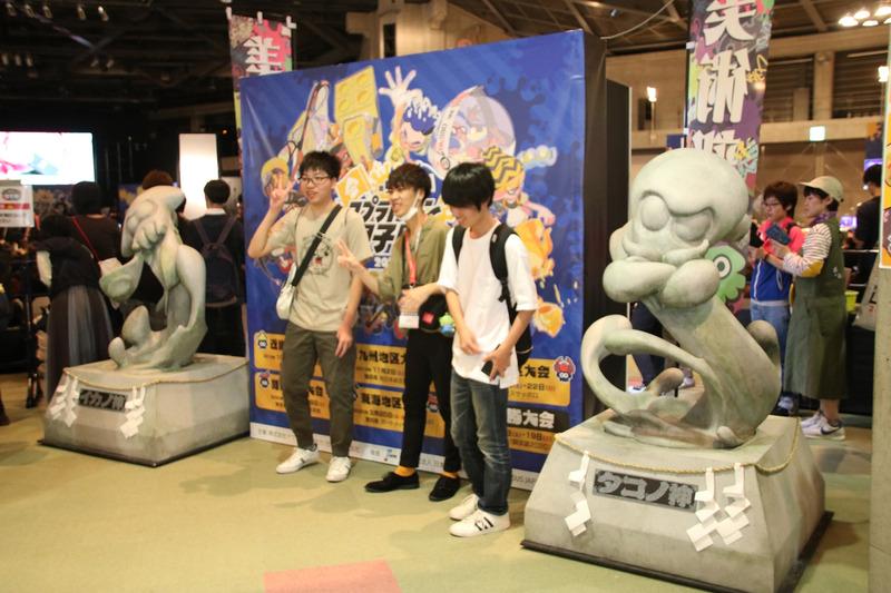 スプラトゥーン甲子園のキービジュアルをバックに、「イカノ神」と「タコノ神」に挟まれた写真が撮れる「写真部」