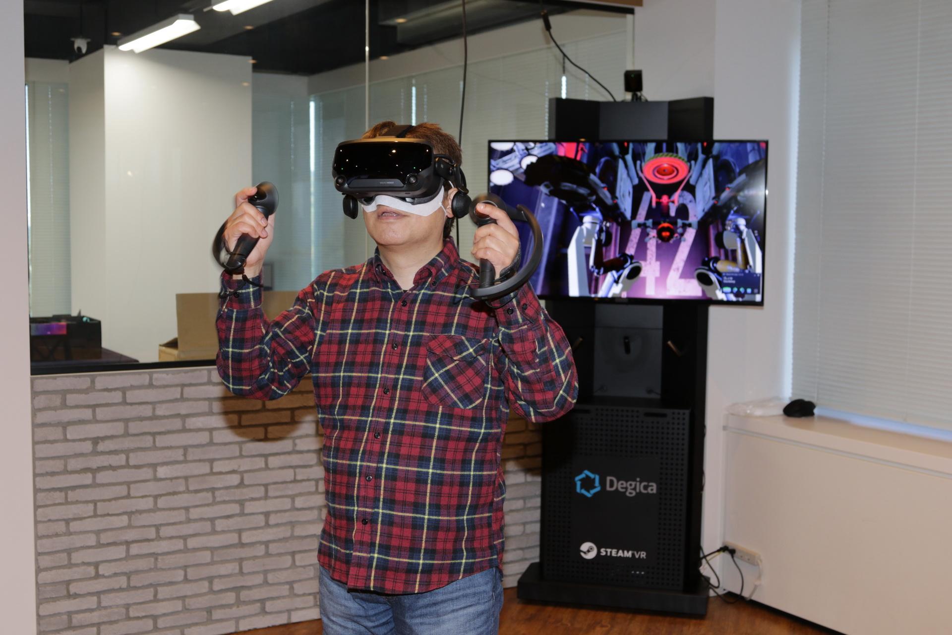 VR体験中。後ろの画面のように、2本の手があるロボットに言われるまま、手を上げたりして操作していく