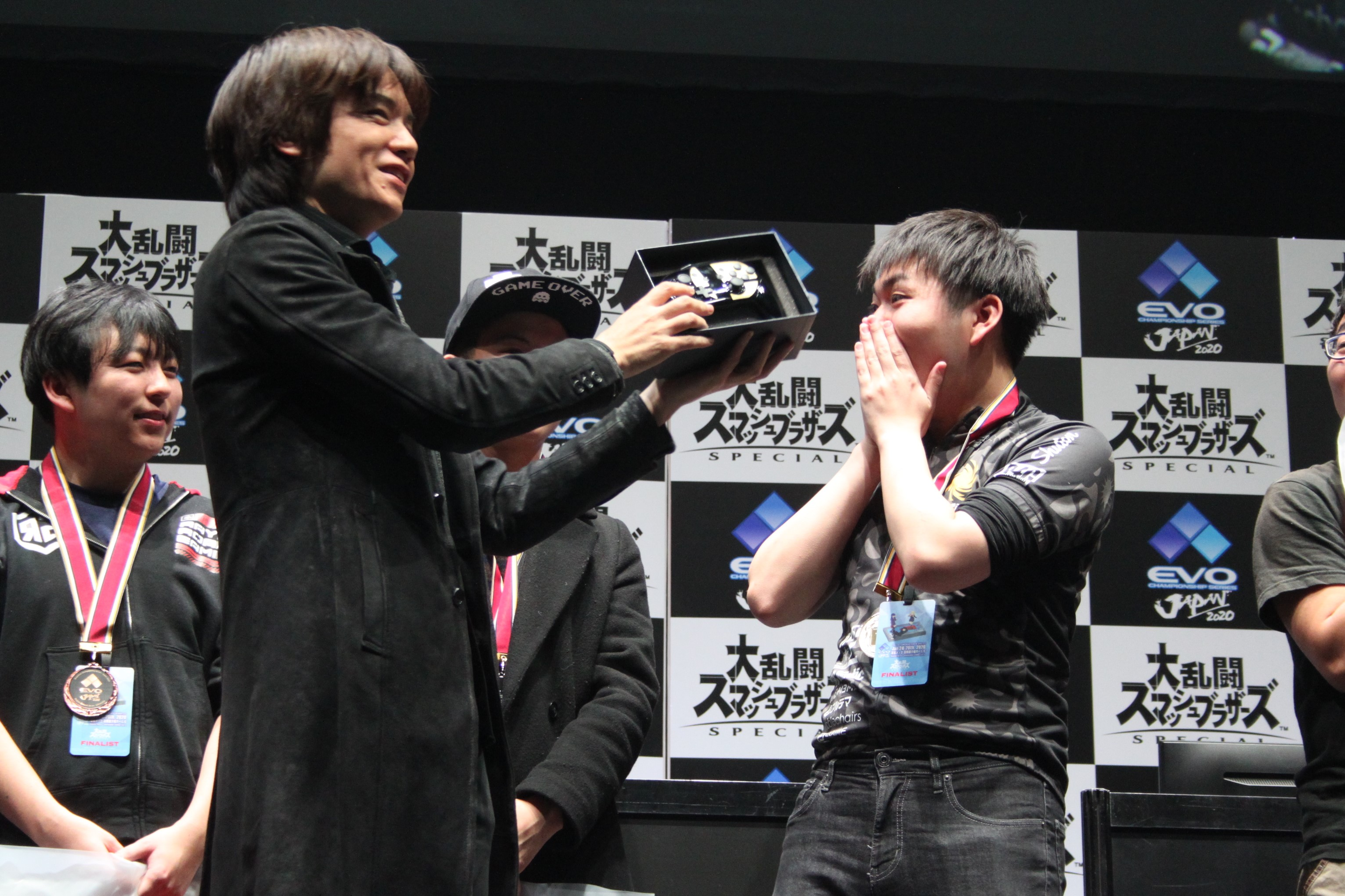 桜井氏からコントローラーを受け取るShuton選手
