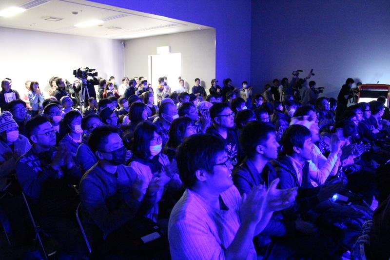大会に参加した格ゲーマーや一般観客が試合の行方を見守っている