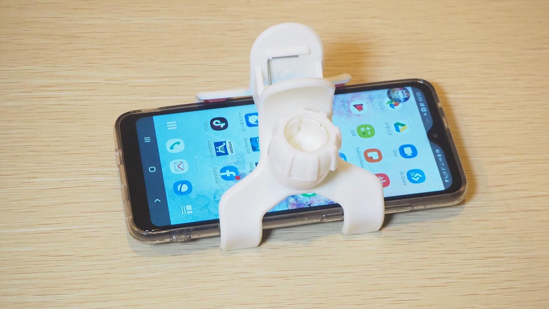 スマートフォンホルダーは、大きな洗濯ばさみみたいになっており、このようにスマートフォンを挟んで使う