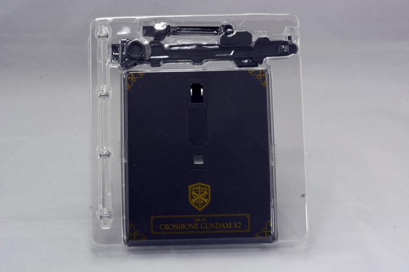 """武器や台座など、4つのブリスターパッケージと、1つの素体が収められたボックスで構成されている。クロスボーンガンダムはギミック満載な上、布製の""""マント""""と、X2ならではの追加武器が封入されており、付属品はかなり多めだ。"""