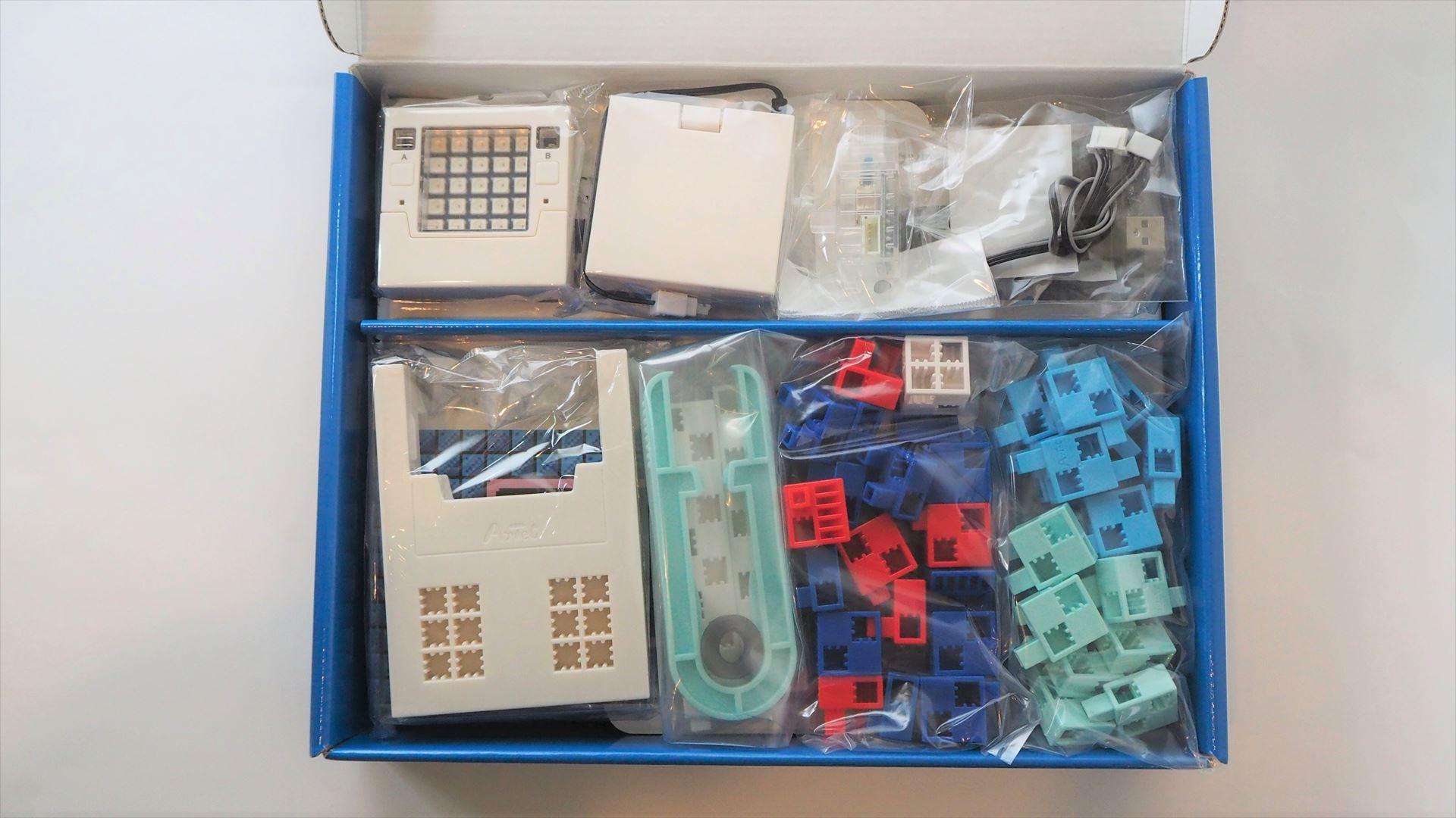 パッケージをあけたところ。上段には、マイコンボード「Studuino:bit」や電池ボックス、ケーブルなどが入っており、下段にはブロックパーツが入っている