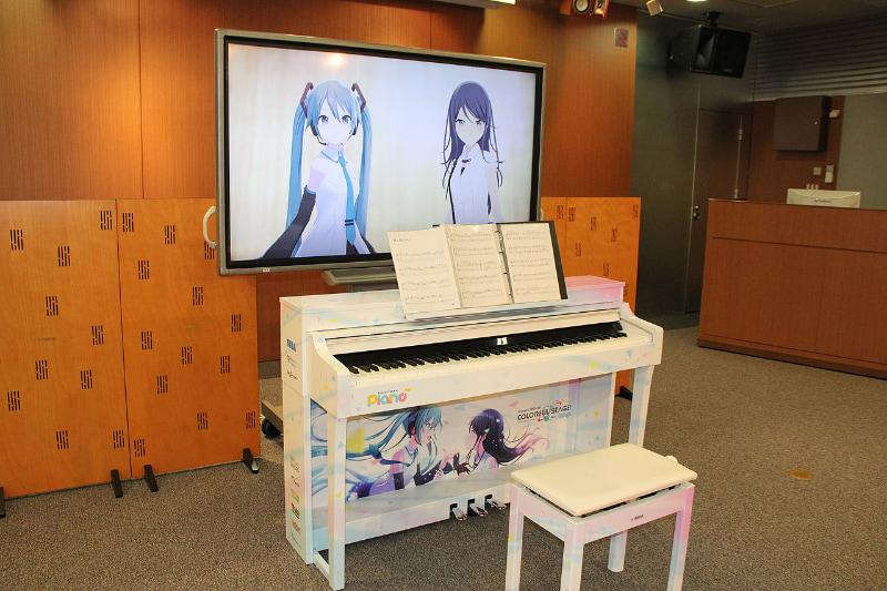 約60インチクラスのモニターが置かれ、画面にはミクさんと一歌が映っている