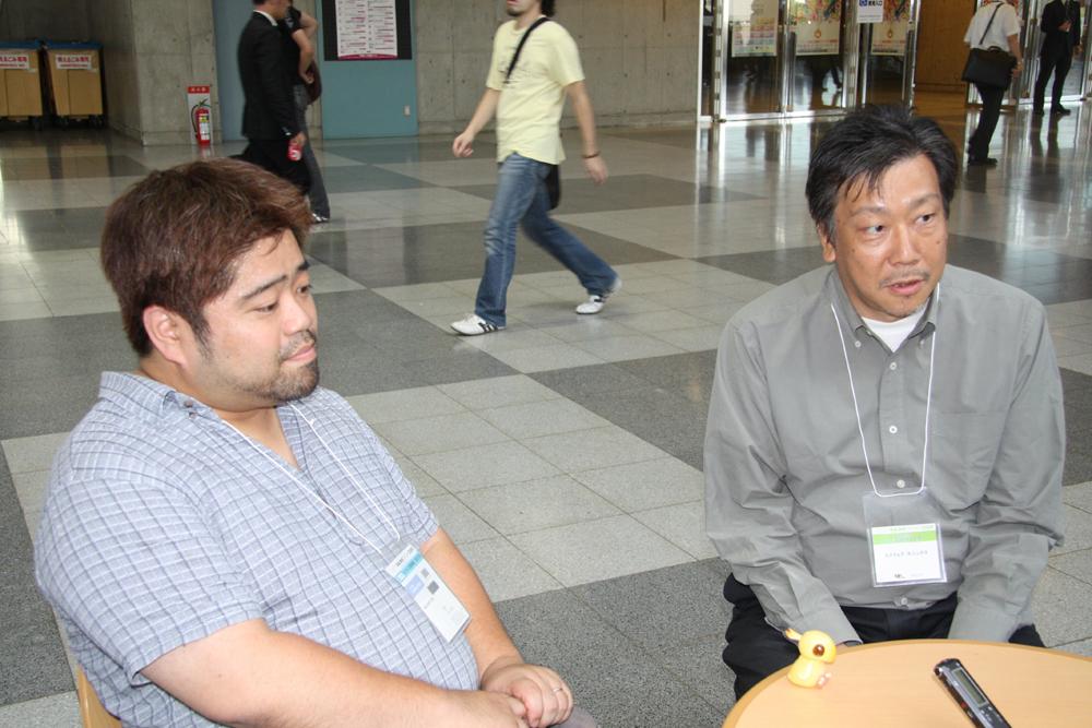 インタビューに応じていただいたプロデューサーの田中弘道氏(右)と、ディレクターの河本信昭氏(左)。幕張メッセのロビーで行なった