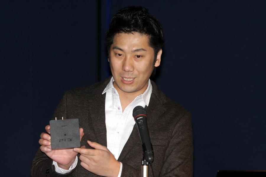「torne」の商品説明を行なう開発を担当した西沢氏。左写真が地デジチューナー部分。右写真はPS3にインストールするためのディスク。インストールするとクロスメディアバーに「テレビ」の項目が現われ「torne」が利用できるようになる