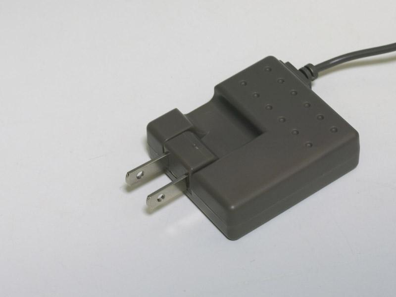 シンプルなACアダプターだが、コンセントプラグを180度に可動できるところや、ケーブルを束ねるマジックテープがついているなど、細かな工夫が嬉しい。写真中央はDSi付属のACアダプターと並べてみたところ。比較するとコンパクトさがわかる