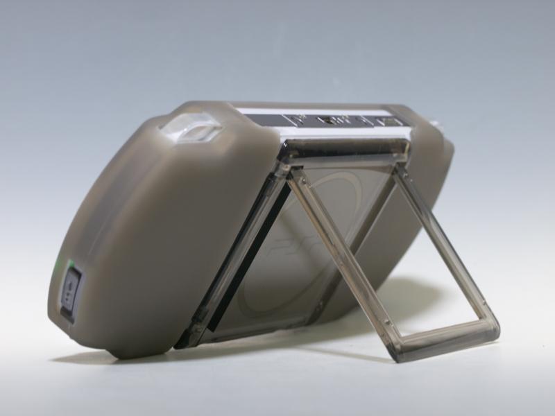 PSP-3000にシリコンカバーと「スクリーン保護プレート」、「背面プロテクトカバー」を装着したところ。一体感があり、特に背面はプロテクトカバーの透明感が目を引く。写真右のように「背面プロテクトカバー」にはスタンドが収納されている
