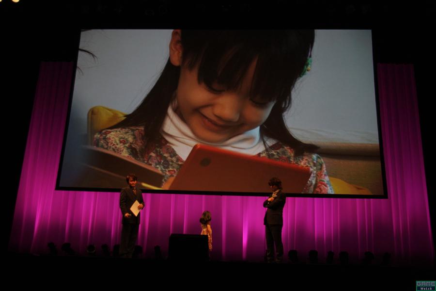 現在3バージョンが放映中のTVCMキャラクタを務める天才子役の芦田愛菜さんがゲストで登場。ステージ袖から登場するなり、会場のあちこちから「かわぃい~!!」と女性ユーザーの嬌声が上がる。大変だったことをきかれると「1日でCMを3つとったんで大変でした」と実にハキハキとした回答。メイキング映像が流されると「ちょっと恥ずかしいです」とはにかんだ表情。クリスマスに欲しいものを聞かれると「今フエルトでぬいぐるみを作っているので、そのためのフエルトが一杯欲しいです。あと、あの、ぬいぐるみの目になるボタンを、欲しいなーって思ってます」とのこと。ゲームのPRも含め、すべてが自然かつ完璧。本当に恐れ入りました