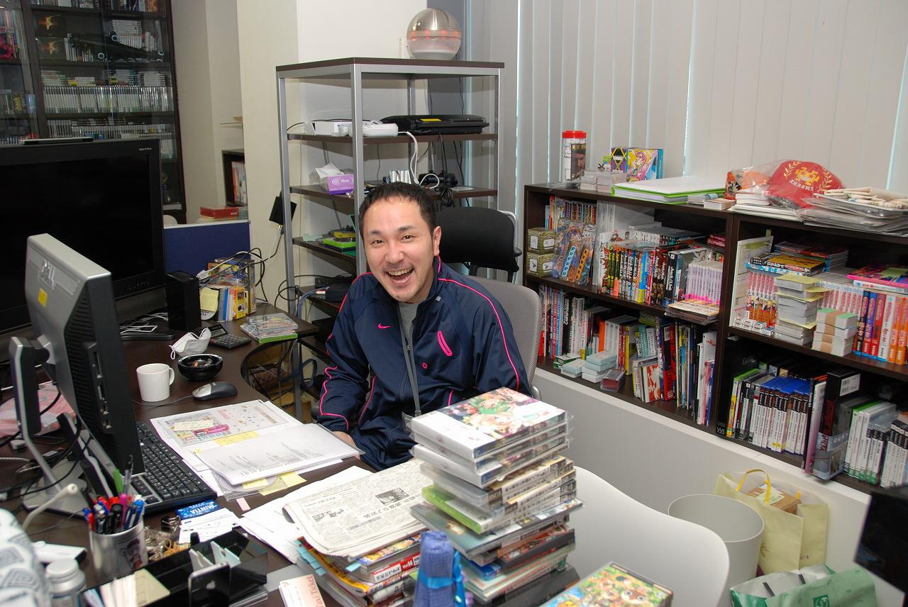 社長室。机にはゲームソフトや漫画などが大量に積まれている