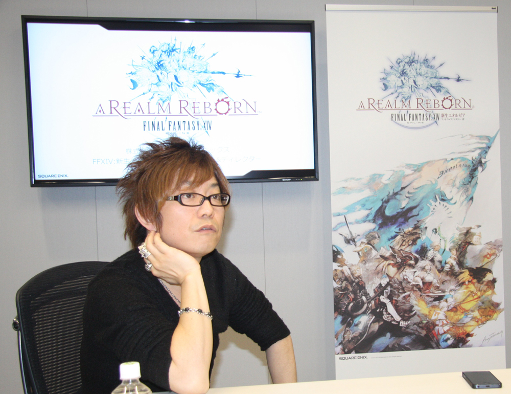 「FFXIV: 新生エオルゼア」プロデューサー/ディレクターの吉田直樹氏。後ろに見えるのはフリーカンパニーをあしらった新デザインのポスター