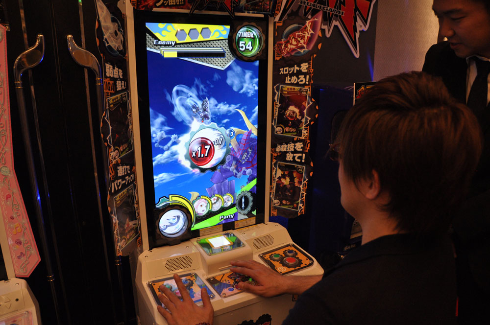 """巨大な武器で巨大なモンスターに立ち向かうという""""デカイ""""がキーワードのゲーム。カードを読み込ませて継続プレイが可能で、戦闘を経て成長し、外見が変化した武器が描かれたチケットが印刷される。武器は剣、銃、ハンマーの3系統。戦闘シーンはカメラアングルが頻繁に変わったり、エフェクトも派手で見応えがある。3DS向けの無料アプリを配布し、そのプレイ結果もゲームに反映できるという"""