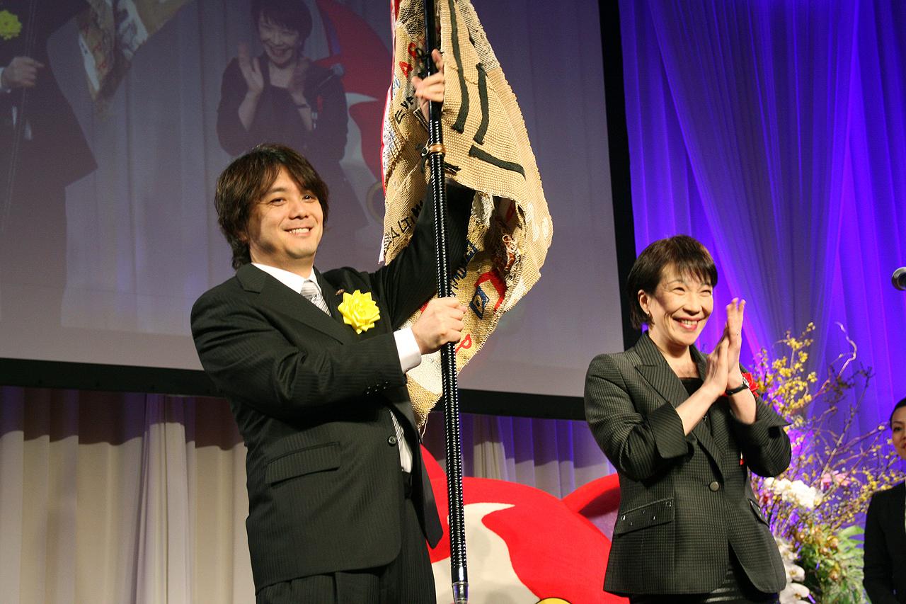 毎回受け継がれる受賞の記念フラッグが日野氏に手渡された