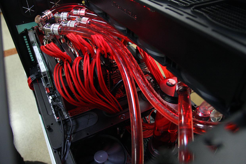 """「GeForce GTX 980」を3枚セットし、ごついパイプを張り巡らせ水冷で動作させている、まさに""""漢の夢PC""""とも言える特別仕様のデモマシン。ディスプレイ込みで壱百万円なり! 会場で「GTA Online」のデモンストレーション用に使用されるほか、空いた時間に来場者がプレイすることも可能"""