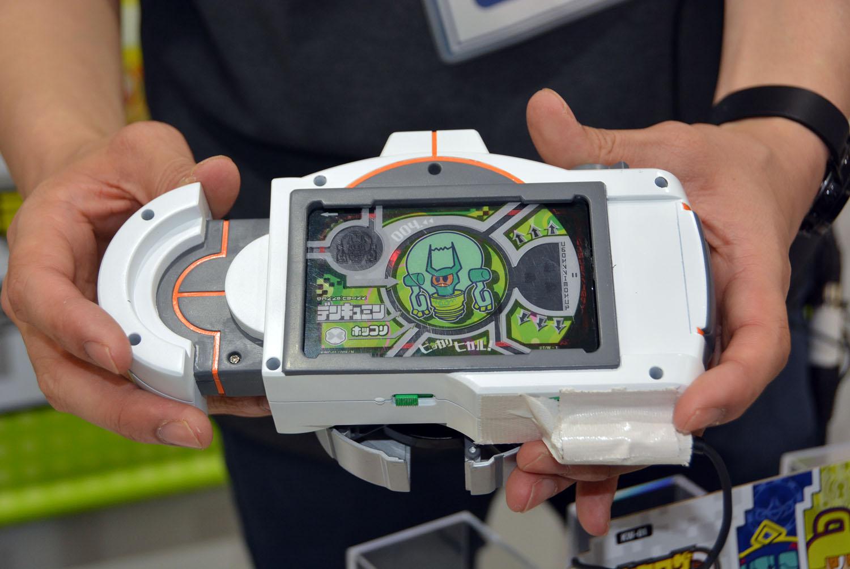 「カミワザワンダ」のキーアイテムであるカメラ型ガジェット「カミワザショット」。中央にICカード内蔵のプラスチック製カード「カミワザプロカ」をセットしている