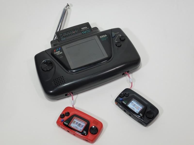 巨大なゲームギアのストラップとして小さな「ゲームギアミクロ」を2台装着。完動品のゲームギアをお持ちの方は、是非このスタイルであえてオリジナルのゲームギアでゲームをプレイしてみてほしい