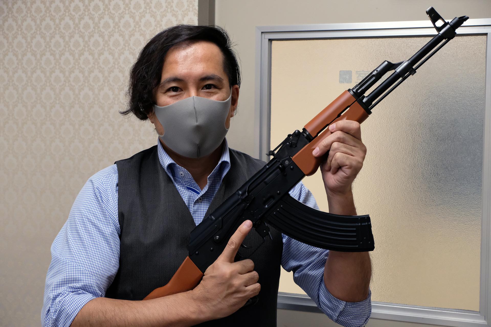 「ガスブローバックマシンガン AKM」を構える東京マルイの広報を務める島村優氏。軍服だけでなく、背広や民族衣装など、どんな服でも似合うのがAKの大きな魅力と言える
