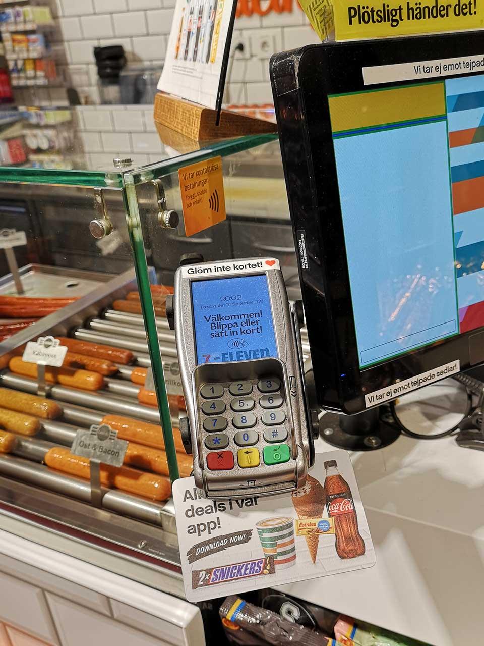 スウェーデンのコンビニエンスストア。欧州だと、多くの店でこのように客側にリーダーを置いてあるので、店員に「クレジットカードで」というだけいい。接触IC、非接触ICのどちらでも使えるので、客が好きな方法で支払う。扇型の電波のようなマークがNFC Pay対応の印