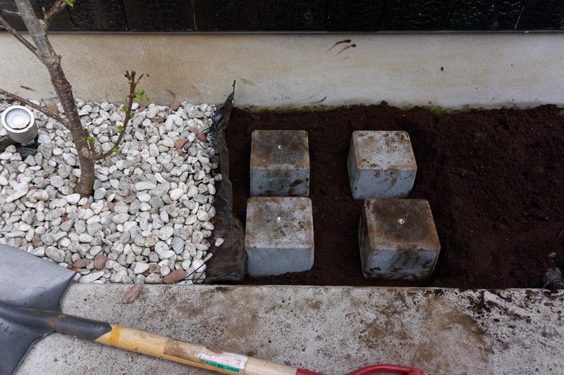 砂利をよけ、土を掘って万能ウエイトを埋設。雨天時に水没しない高さにすることも重要だ