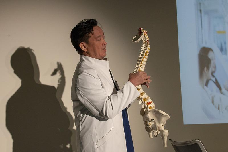 模型を用いて説明する酒井氏。模型は平常時の首から背中の様子