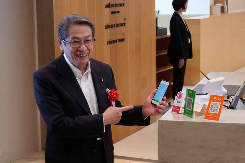 キックオフイベント終了後、実際にコード決済を体験する石田総務大臣。とても簡単で便利と評価していた