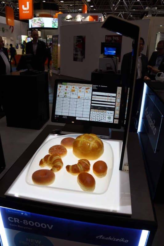 画像認識によるパンの自動会計システムを開発するブレインは、旭精工のパートナーシップにともなって現地の協力パートナーのCoinmasters BVのブースで展示を行なう