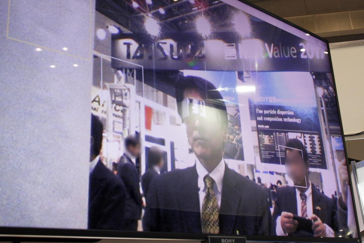 「PrivacyVisor」はサングラスのようにかけるだけで防犯カメラなどの顔検出を回避できる。右下の人の顔には顔として検出していることを示すフレームが表示されているが、「PrivacyVisor」をかけた中央の人の顔には表示されていない(ぼかし加工は、編集部で施したものです)