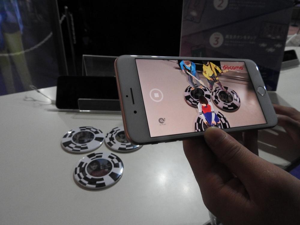 NTTドコモがデモしていた「ミニチュア3Dライブ」。スマホに専用アプリをダウンロードし、丸い缶バッジの上にかざすことで、画面にメンバーの3D CGが表示され、演奏が開始する